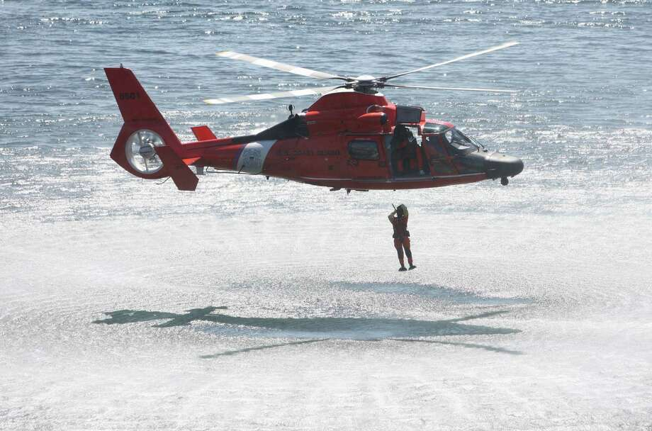 A file photo shows a U.S Coast Guard rescue swimmer leaping from a Coast Guard helicopter during the annual Seafair Fleet Week Parade of Ships on Wednesday, August 1, 2012 on Elliott Bay. Photo: JOSHUA TRUJILLO / SEATTLEPI.COM