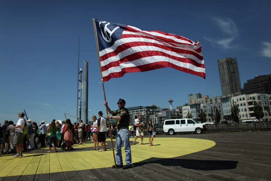 A protester holds a flag on the Seattle waterfront during the annual Seafair Fleet Week Parade of Sh