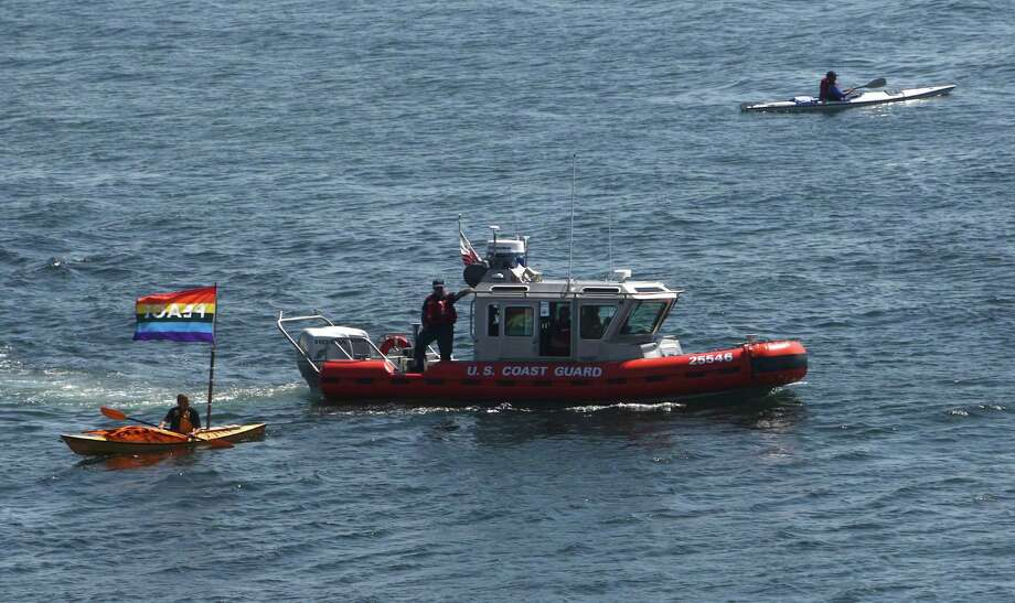 A Coast Guard boat passes near protesters during the annual Seafair Fleet Week Parade of Ships on Wednesday, August 1, 2012 on Elliott Bay. Photo: JOSHUA TRUJILLO / SEATTLEPI.COM