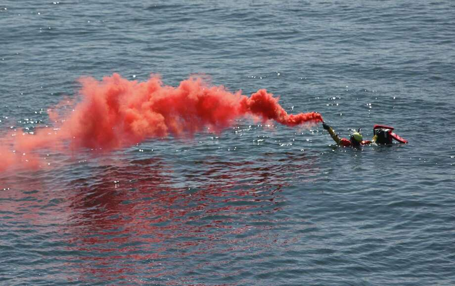 A rescue swimmer uses a smoke signal during a rescue demonstration at the annual Seafair Fleet Week Parade of Ships on Wednesday, August 1, 2012 on Elliott Bay. Photo: JOSHUA TRUJILLO / SEATTLEPI.COM