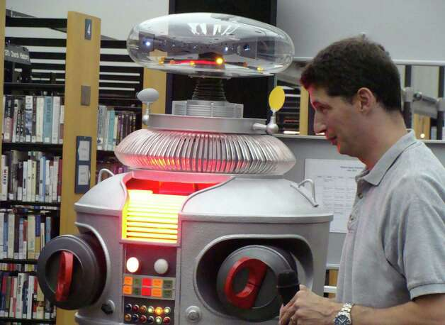 "Mike Ogrinz listens to the replica of the B9 robot from the television show ""Lost in Space"" that he made as it speaks to an audience Wednesday at the Westport Public Library. Photo: Meg Barone / Westport News freelance"