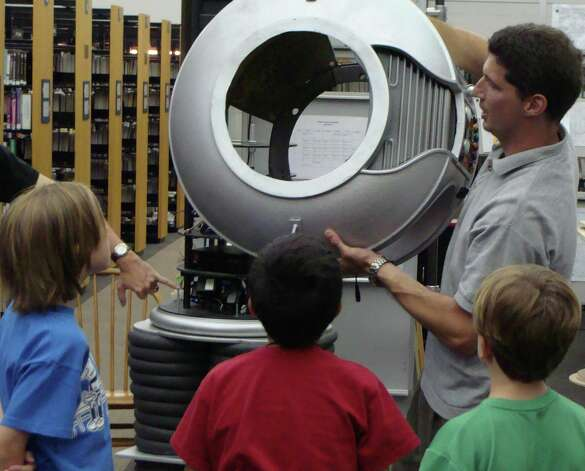 Curious children had a chance to look inside the torso of a B9 robot Wednesday as its maker, Mike Ogrinz, disassembled it during his presentation at the Westport Public Library. Photo: Meg Barone / Westport News freelance