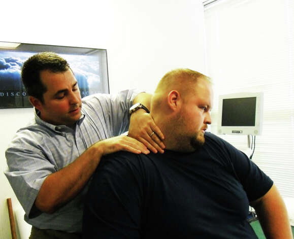 Chiropractic sports physician Dr. Craig Sollose applies pressure on the neck of John Lasczak, an offensive lineman for Western Connecticut Militia football team and an auto mechanic in Danbury. Lasczak is being treated for heel and neck pain with a myofasical technique called applied resistance technique (ART) to help alleviate pain in various areas of the body. Photo: Carol Kaliff