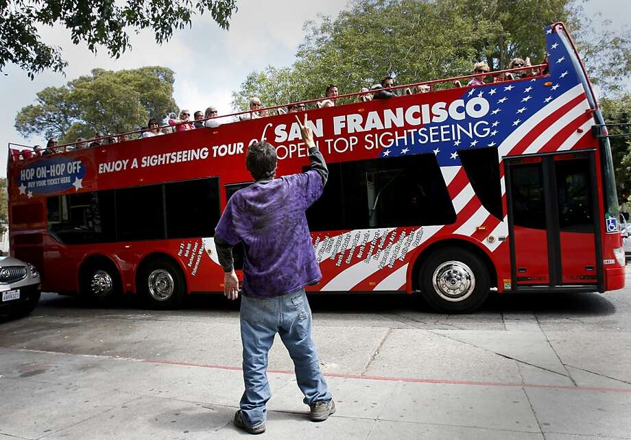Roland Dequina flashes the peace sign to tourists on a bus heading down Haight Street. Dequina, who has received 25 citations under San Francisco's sit/lie ban, has lived on the Haight's sidewalks since 1997. Photo: Brant Ward, The Chronicle