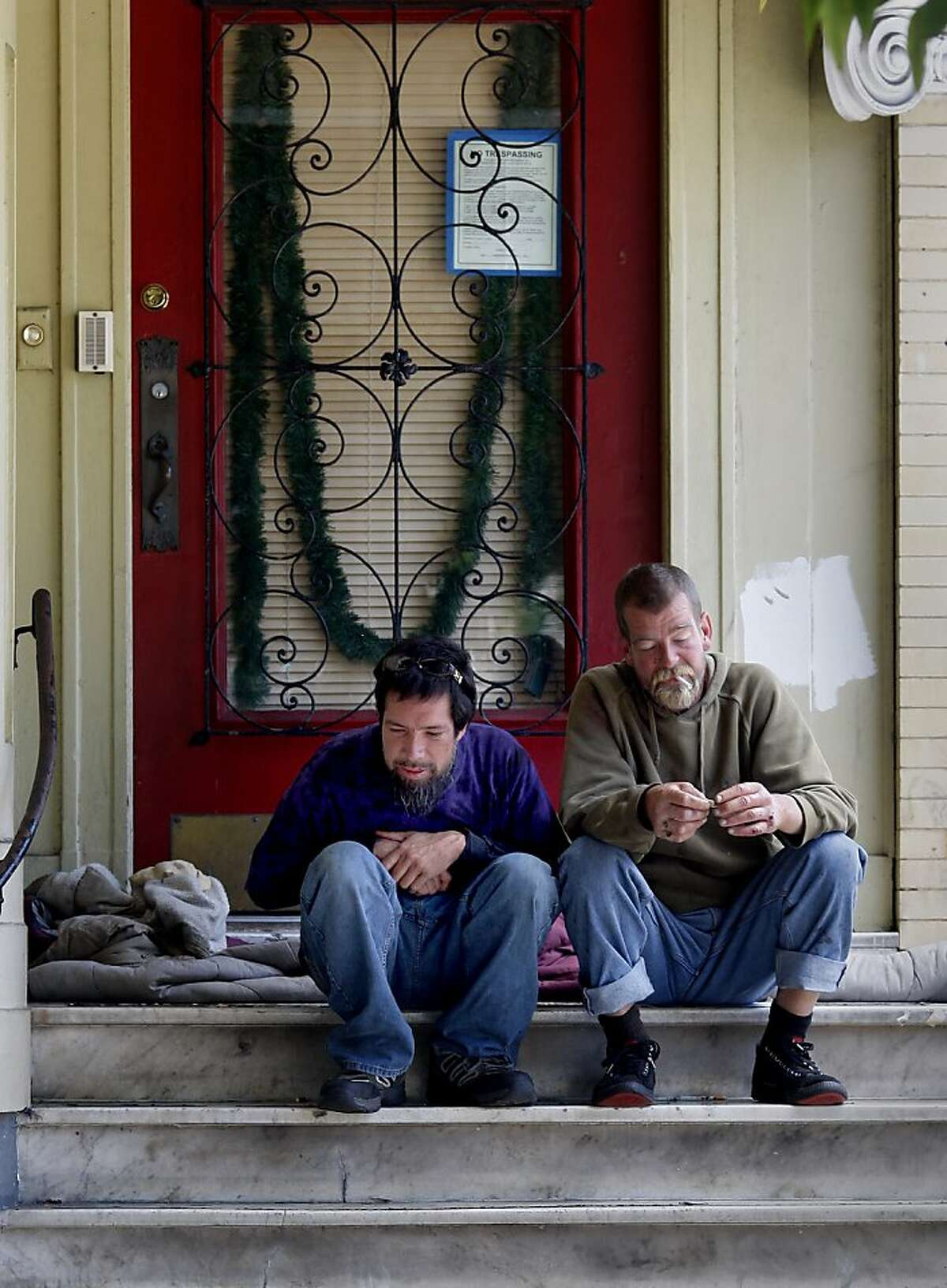 Dequina (left) and Justin O'Brien, who has 34 sit/lie citations, rest on the steps of a Catholic church building.