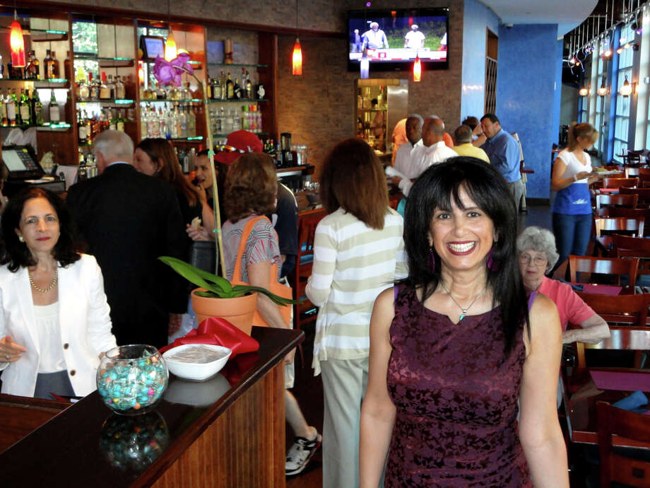 Nitzy Cohen poses in the main dining area of her new Atlas restaurant and bar, which celebrated its grand opening in South Norwalk,Conn. on July 25, 2012. The restaurant will feature international cuisine and the music of the 1970s and 1980s because Cohen said most of the clubs in Norwalk cater to the younger crowd and she wanted to create an atmosphere that would be welcoming to a wider age range Photo: Meg Barone / Stamford Advocate Freelance