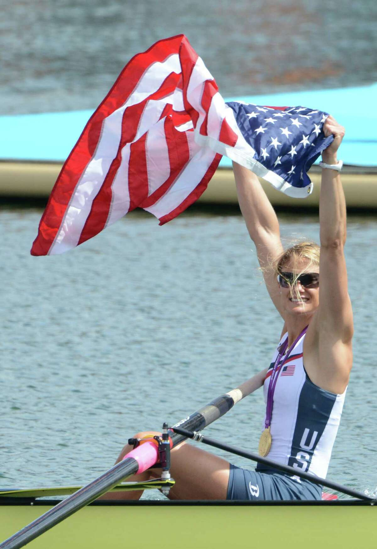 A member of the US team waves her national flag as she celebrates after receiving their gold medals won in the women's eight final of the rowing event during the London 2012 Olympic Games, at Eton Dorney Rowing Centre in Eton, west of London, on August 2, 2012. AFP PHOTO / DAMIEN MEYER