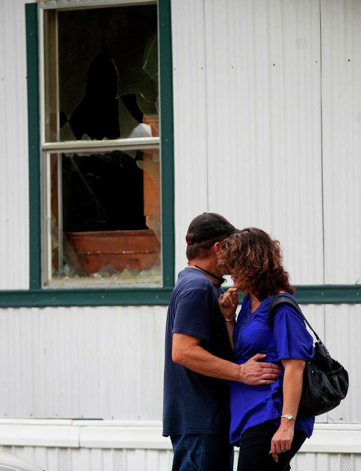 A man comforts a woman outside a trailer home after it caught fire at Pinewood Place trailer park Thursday, Aug. 2, 2012, in Tomball. Firefighters received the call at 7:41 a.m., and we're notified by family members upon arrival that a 4-year-old was still inside, Klein Volunteer Fire Department District Chief David Bessolo said. Family members had cuts and abrasions when firefighters arrived after trying to break out a window to retrieve the 4-year-old was that was still inside. Six people were transported to Tomball Regional Hospital with the 4-year-old in critical condition and the five others in stable condition. Photo: Cody Duty, Houston Chronicle / © 2011 Houston Chronicle