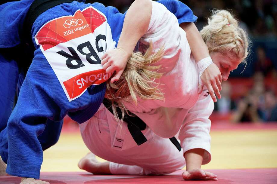USA's Kayla Harrison (white) competes with Great Britain's Gemma Gibbons (blue) during the gold-medal match in the Women's Judo 78 kg division at the ExCeL Centre during the 2012 Summer Olympic Games in London, England, Thursday, August 2, 2012. Kayla Harrison defeated Great Britain's Gemma Gibbons to win the Gold Medal.  (Harry E. Walker/MCT) Photo: Harry E. Walker, McClatchy-Tribune News Service / Harry E. Walker, Copyright 2012