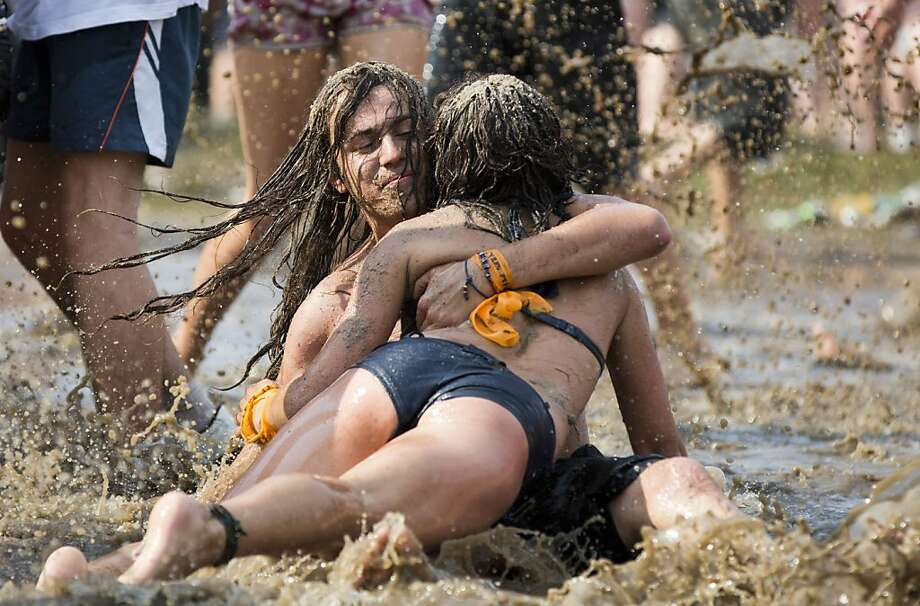 "Don't take the brown acid, man:A couple dive into a huge mud puddle at Prznek Woodstock (Polish for ""Woodstock Station"") near the Polish-German border in Kostrzyn, Poland. Photo: Gero Breloer, Associated Press"