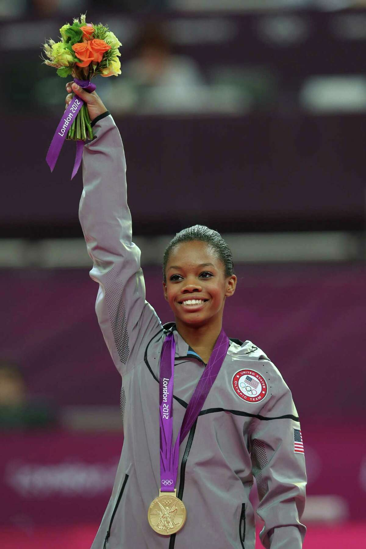 LONDON, ENGLAND - AUGUST 02: Gabrielle Douglas of the United States celebrates on the podium after winning the gold medal in the Artistic Gymnastics Women's Individual All-Around final on Day 6 of the London 2012 Olympic Games at North Greenwich Arena on August 2, 2012 in London, England.