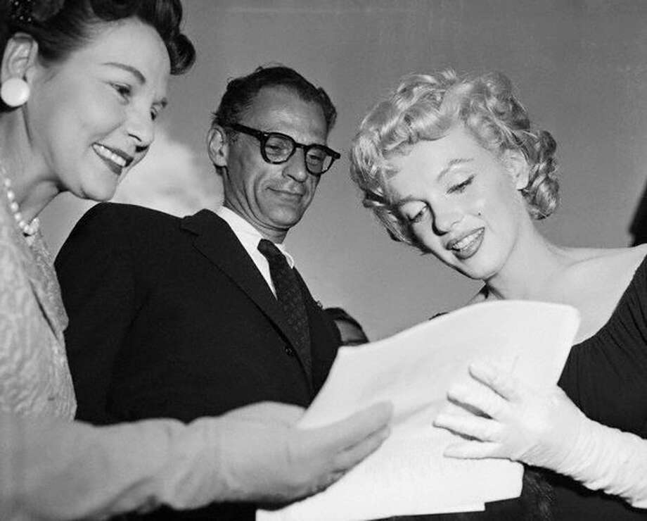 While her husband, playwright Arthur Miller, looks on, actress Marilyn Monroe (R) signs an autograph for a fan in New York in this May 21, 1958, file photo. Photo: Bettmann/Corbis, REUTERS / Bettmann / Corbis