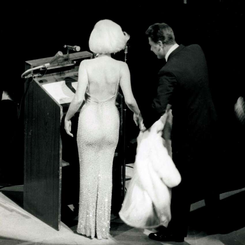 In this May 19, 1962 publicity photo provided by Running Press, Peter Lawford, right, tends to Marilyn Monroe's fur as she prepares to sing