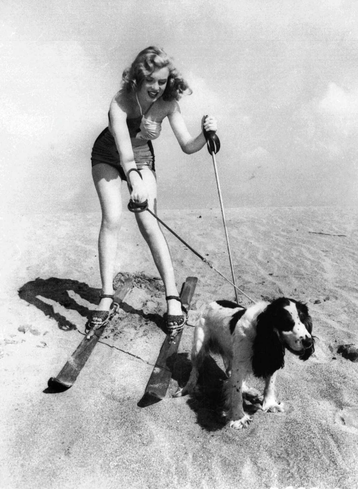 In this January 1, 1947 file photo, starlet Marilyn Monroe plays at the beach with her dog Ruffles.