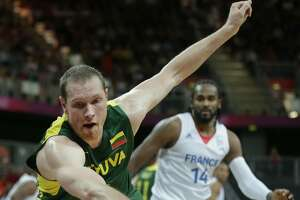 Lithuania's Darius Songaila chases after a loose ball against France's Ronny Turiaf during a men's basketball game at the 2012 Summer Olympics, Thursday, Aug. 2, 2012, in London. (Charles Krupa / Associated Press)
