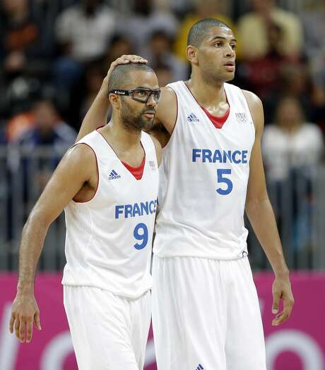 France's Nicolas Batum (5) pats teammate France's Tony Parker (9) on the head during a preliminary men's basketball game against Lithuania at the 2012 Summer Olympics, Thursday, Aug. 2, 2012, in London. (Eric Gay / Associated Press)