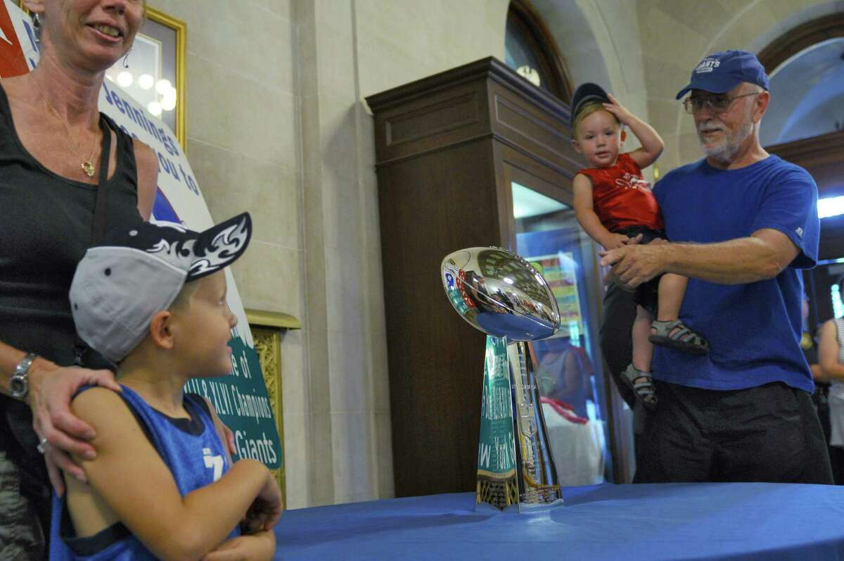 Charlie Kovage of Hoosick Falls shows his grandson Russell Stifter, 2, the NFL's Vince Lombardi Trophy that the New York Giants received after winning last season's Super Bowl, in the rotunda of City Hall on Thursday Aug. 2, 2012 in Albany, NY. Charlie has been rooting for the Giants since 1954. His wife, Sharon, far left, stands with their other grandson Rich Stifter, 5, lower left. (Philip Kamrass / Times Union)