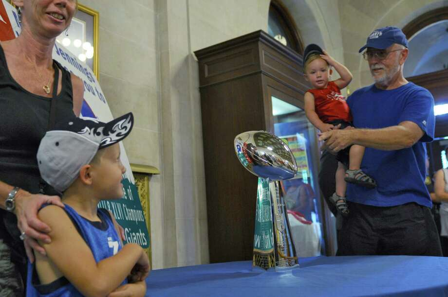 Charlie Kovage of Hoosick Falls shows his grandson Russell Stifter, 2,  the NFL's Vince Lombardi Trophy that the New York Giants received after winning last season's Super Bowl, in the rotunda of City Hall on Thursday Aug. 2, 2012 in Albany, NY.  Charlie has been rooting for the Giants since 1954. His wife, Sharon, far left, stands with their other grandson Rich Stifter, 5, lower left. (Philip Kamrass / Times Union) Photo: Philip Kamrass / 00018690A