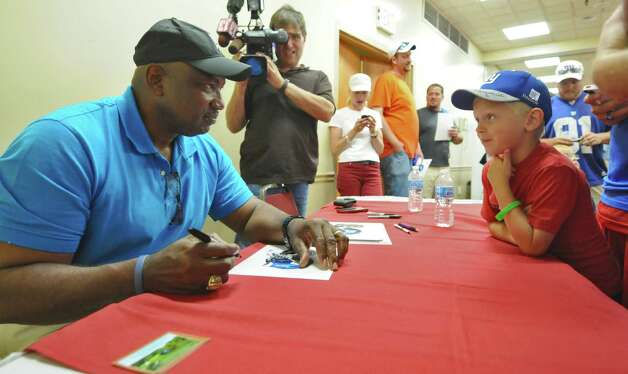 New York Giants great George Martin signs an autograph for lifelong Giants fan Ayden Swears of Fort Edward, 8, after his father, Phil, gave blood during the American Red Cross New York Giants Training Camp Blood Drive at the Best Western, on Thursday Aug. 2, 2012 in Albany, NY.  (Philip Kamrass / Times Union) Photo: Philip Kamrass / 00018634A