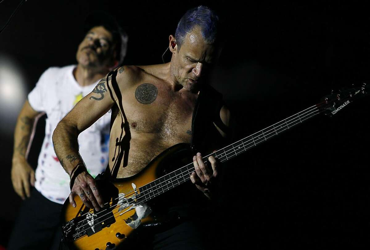 """Red Hot Chili Peppers' Mike """"Flea"""" Balazary, right, and Anthony Kiedis, left, perform during the Rock in Rio music festival in Arganda del Rey, on the outskirts of Madrid, Spain, Sunday, July 8, 2012. (AP Photo/Andres Kudacki)"""