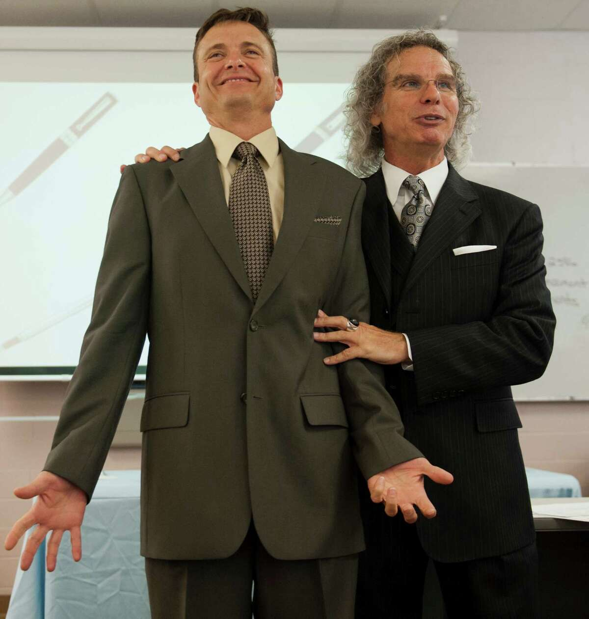 Col. Jeffrey Brlecic, left, receives a critique that his suit is too long from master tailor Sofio Barone in Fort Meade, Md., for a military image-consulting program for officers entering civilian life.