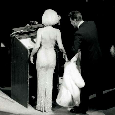 "Marilyn Monroe takes to the stage at Madison Square Garden to sing ""Happy Birthday"" to Presideint John F. Kennedy who was turning 45 in 1962. Peter Lawford tends to Monroe's fur wrap. She was the last act of the evening that included performances from Maria Callas, Jack Benny, Peggy Lee, Harry Belafonte and Shirley MacLaine. ""There was a hush over the whole place when I came on to sing,"" Monroe told Life magazine two months later. ""Like if I had been wearing a slip I would have thought it was showing or something. I thought, 'Oh, my gosh, what if no sound comes out?!"" Monroe's dress, designed by Jean Louis was flesh-hued and sheer and covered with 4,000 rhinestones. She paid Louis $5,000 to create the ""historic"" dress. Photo: New Marilyn Monroe / HC"