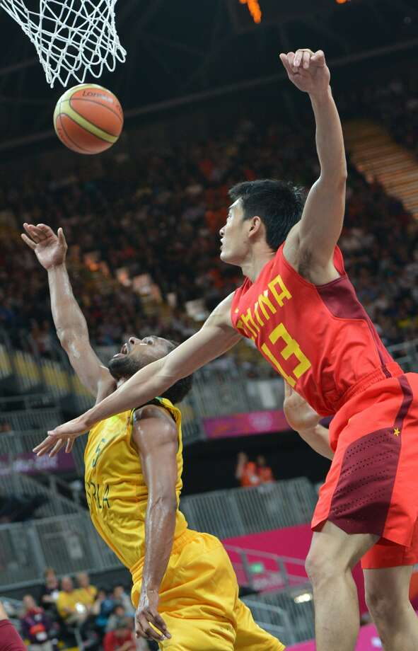 Australian guard Patrick Mills (L) fights for the ball with Chinese guard Chen Jianghua during the men's preliminary round Groupe B basketball match Australia vs China of the London 2012 Olympic Games  on August 2, 2012 at the basketball arena in London. Australia won 49-23. (MARK RALSTON / AFP/Getty Images)