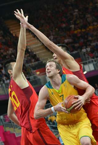 Australian forward Joe Ingles (C) vies with Chinese centre Zhang Zhaoxu and Chinese guard Guo Ailun (R) during the men's preliminary round Groupe B basketball match Australia vs China of the London 2012 Olympic Games  on August 2, 2012 at the basketball arena in London. Australia won 49-23. (MARK RALSTON / AFP/Getty Images)