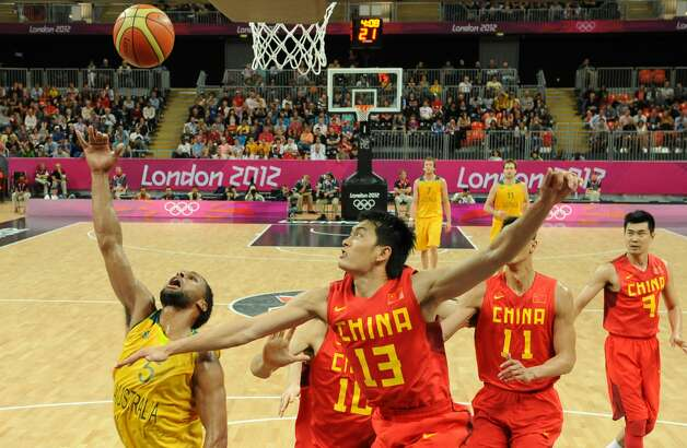 Australian guard Patrick Mills (L) scores against Chinese guard Chen Jianghua (C) during the men's preliminary round Groupe B basketball match Australia vs China of the London 2012 Olympic Games  on August 2, 2012 at the basketball arena in London. Australia won 49-23. (MARK RALSTON / AFP/Getty Images)