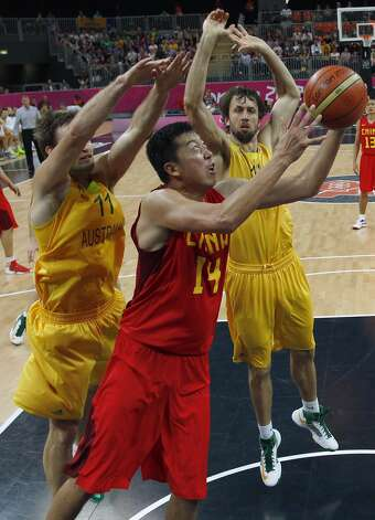 Australia's Mark Worthington (L) and Matt Nielsen (R) try to stop China's Wang Zhizhi (C) during their men's preliminary round Group B basketball match at the Basketball Arena during the London 2012 Olympic Games August 2, 2012. (MIKE SEGAR / AFP/Getty Images)