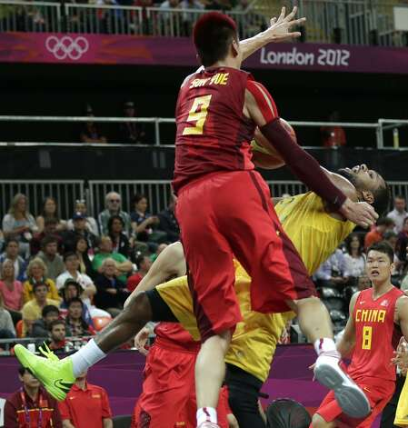 Australia's Patrick Mills tries to get a shot off as he is blocked by China's Sun Yue during a men's basketball game at the 2012 Summer Olympics, Thursday, Aug. 2, 2012, in London. (Charles Krupa / Associated Press)