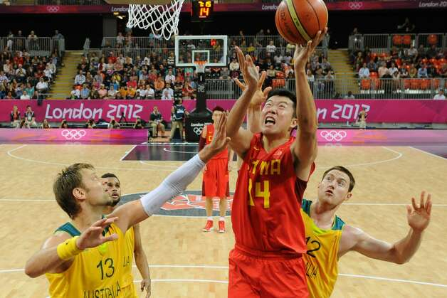 China's Wang Zhizhi (14) shoots to score against Australia's David Andersen (13) and Aron Baynes (12) during a men's basketball game at the 2012 Summer Olympics Thursday, Aug. 2, 2012, in London. (Mark Ralston / Associated Press)