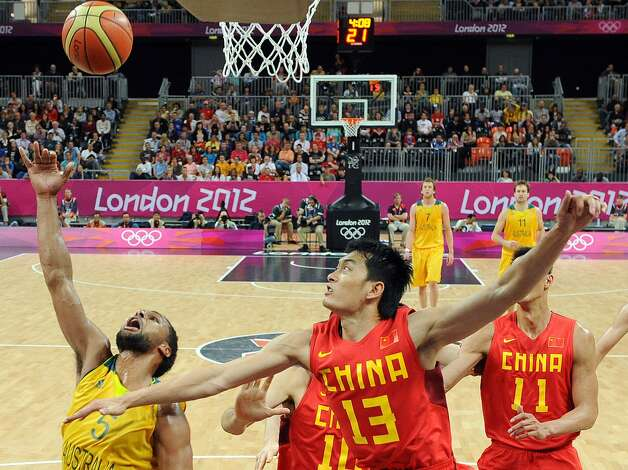 China's Chen Jianghua (13) defends as Australia's Patrick Mills (5) shoots to score during a men's basketball game at the 2012 Summer Olympics Thursday, Aug. 2, 2012, in London. (Mark Ralston / Associated Press)
