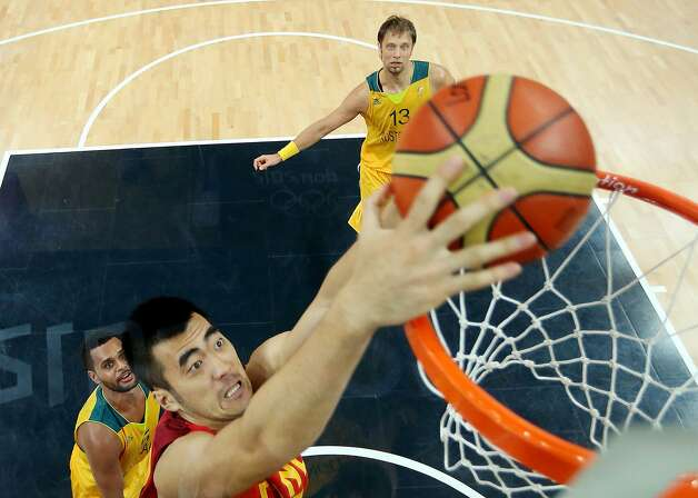 China's Zhaoxu Zhang, foreground, shoots over Australia's Patrick Mills, left,  and David Andersen, top, during a men's basketball game at the 2012 Summer Olympics Thursday, Aug. 2, 2012, in London. (Christian Peterson / Associated Press)