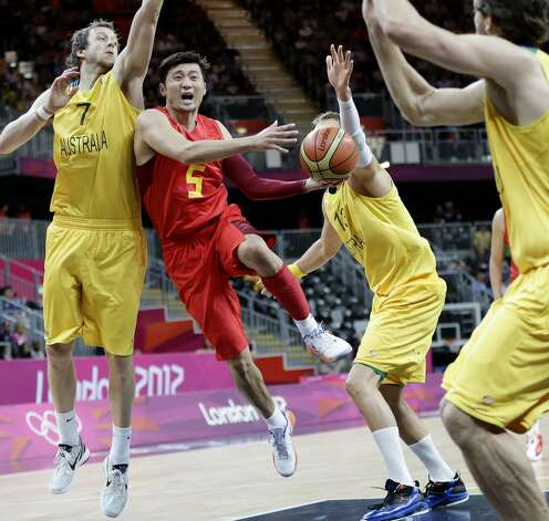 China's Liu Wei (5) drives to the basket ast Australia's Joe Ingles (7) and David Andersen defend during a preliminary men's basketball game at the 2012 Summer Olympics, Thursday, Aug. 2, 2012, in London. (Eric Gay / Associated Press)