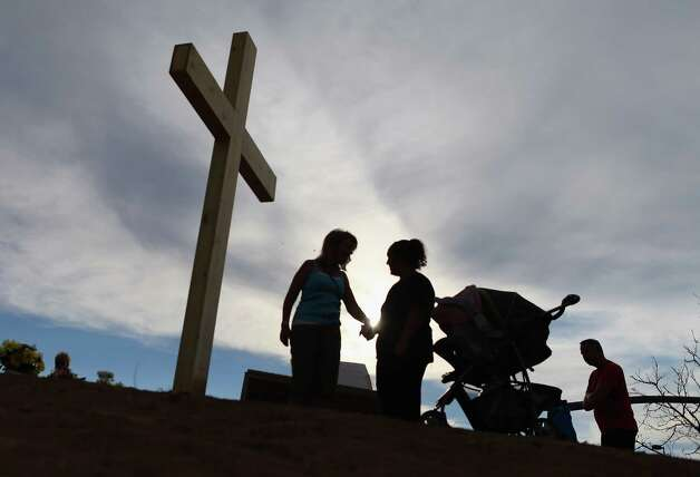 People pray together near a cross erected in a memorial setup across the street from the site of the shootings in Aurora, Colo., where arado. Express-News readers continue to weigh in on gun control. Photo: Joe Raedle, Getty Images / 2012 Getty Images