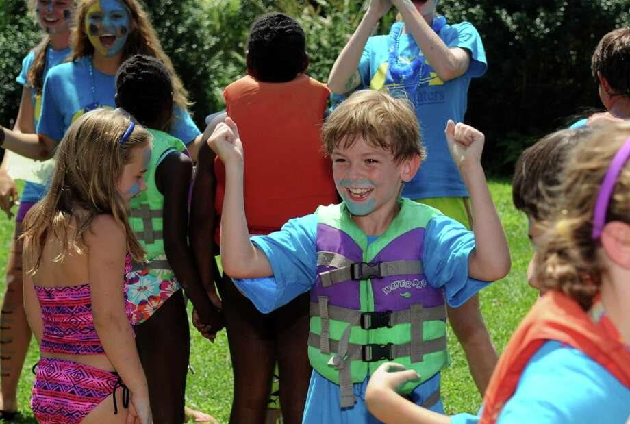 """The """"Bluefish"""" cheer for their teammates during SoundWaters' annual """"Anything That Floats"""" race at Holly Pond in Cove Island Park on Thursday, August 2, 2012. Photo: Lindsay Niegelberg / Stamford Advocate"""