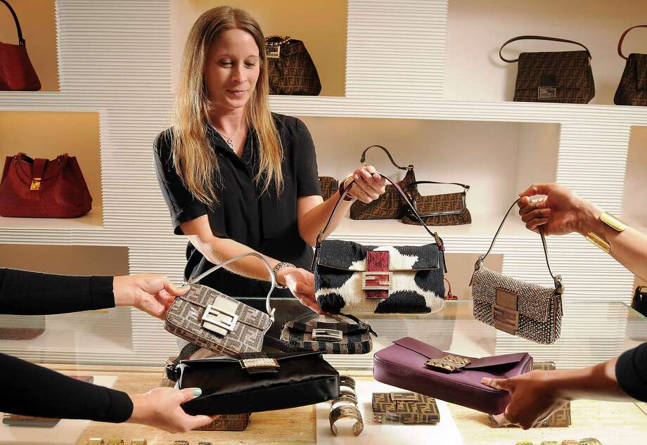 Assistant manager Christy Frederic shows off some Fendi Baguette bags at the Fendi store in the Galleria Friday July 27, 2012.(Dave Rossman/For the Chronicle) Photo: Dave Rossman / © 2012 Dave Rossman