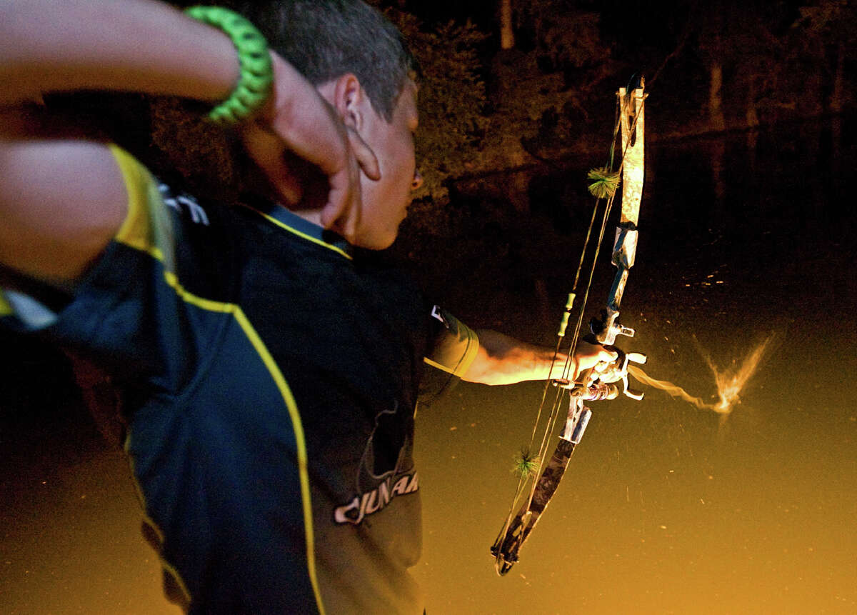 Robert Blackburn, 15, who holds six current adult and 13 junior bowfishing state records, lets one fly.