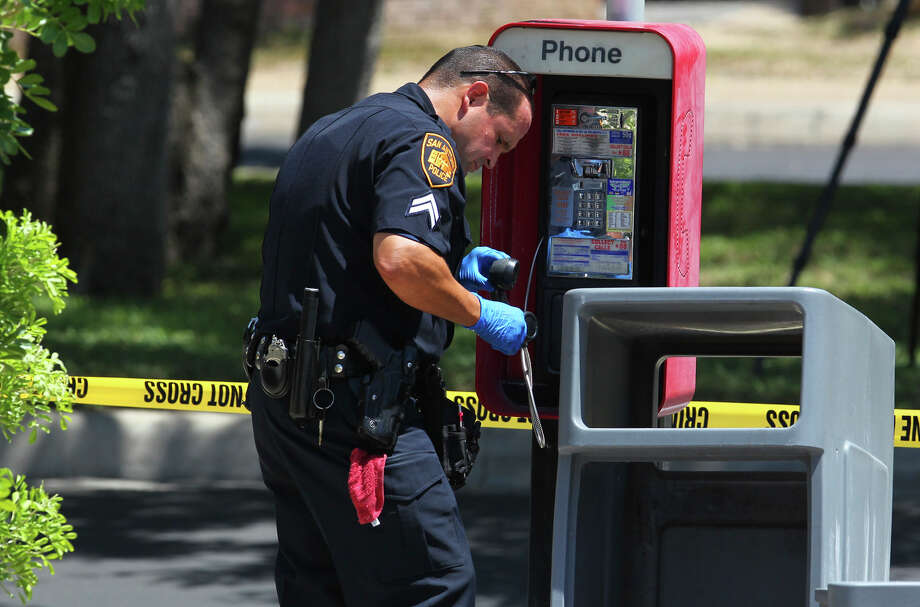 San Antonio police detective Raymond Gallegos gathers evidence Thursday August 2, 2012 from a pay phone at a Shell station on the 13,000 block of Blanco road. Accoding to police department public information officer Javier Salazar, police responded to a call made at the Shell station on Blanco that came in as a 911 call. The call allegedly made a reference to yesterday's bomb threat incident at the San Antonio International Airport. John Davenport/©San Antonio Express-News Photo: John Davenport/© San Antonio Ex, San Antonio Express-News / John Davenport/©San Antonio Exp