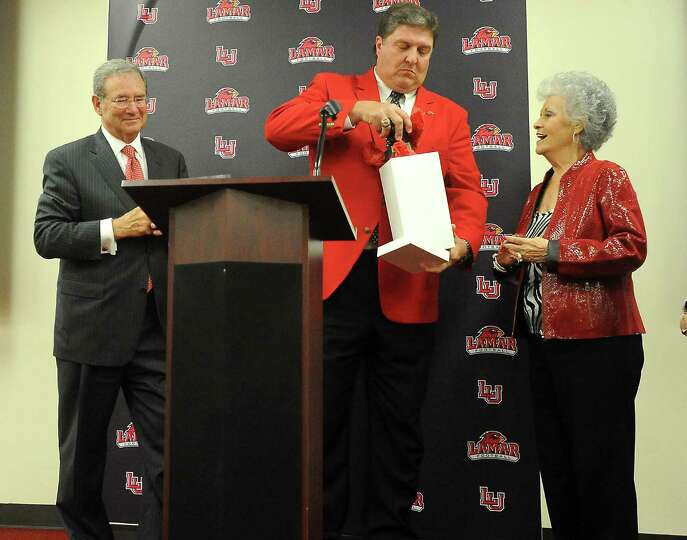 Lamar President, Jimmy Simmons and Cardinal football coach, Ray Woodard offer a gift to Charlene Dau