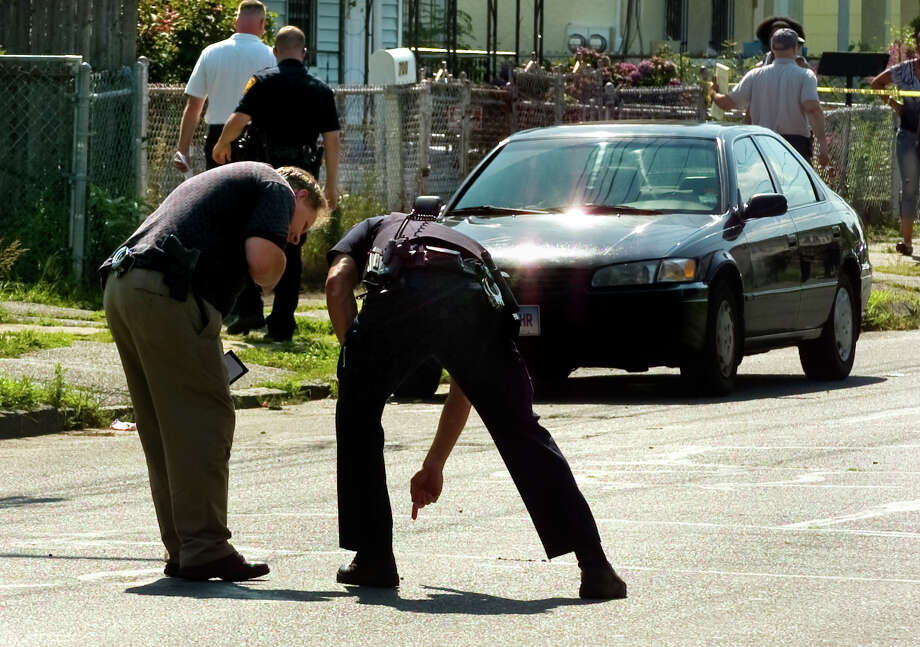 A Bridgeport police detective points to a bullet casing as they investigate the homicide of Gary Gullap, 17, on Hallett and Ogden Streets in Bridgeport, Conn. on Thursday August 2, 2012. Photo: Christian Abraham / Connecticut Post