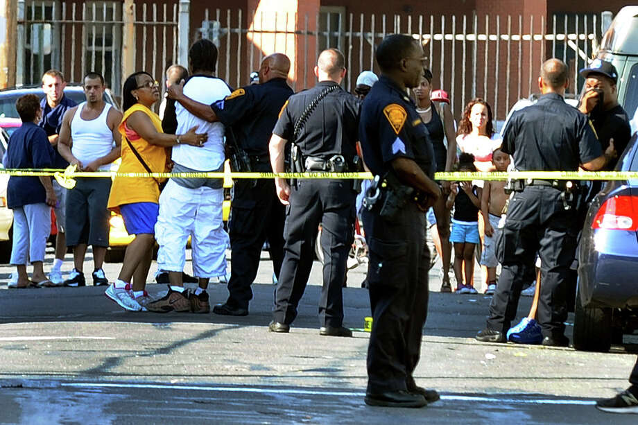 Bridgeport police comfort a man who came to the scene of the homicide of Gary Gullap, 17, on Hallett and Ogden Streets in Bridgeport, Conn. on Thursday August 2, 2012. The homicide is the city's 15th this year and fourth in less than two weeks. Photo: Christian Abraham / Connecticut Post
