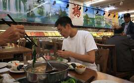 Paul Wang (middle), 22 years old, having lunch with his grandmother as she adds chrysanthemum leaves to the pot at the a hot pot buffet in Oceanview Supermarket  in San Francisco, California, on Wednesday, August 31, 2011.