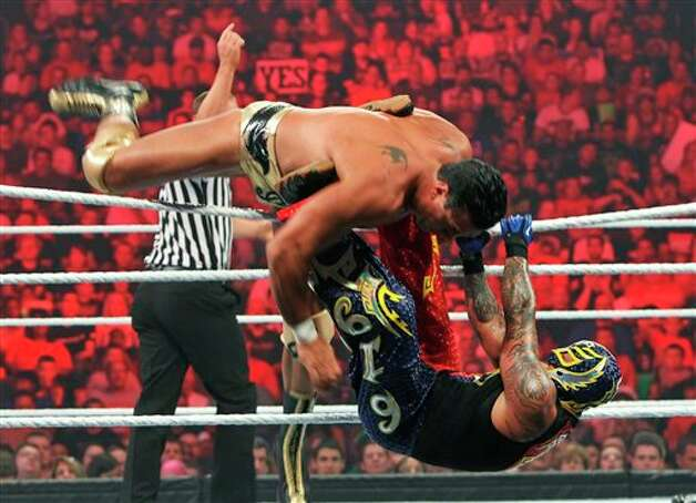 Alberto Del Rio flips over the top of Rey Mysterio as they leave the ring during WWE Monday Night Raw on Monday, July 23, 2012, in St. Louis. (AP Photo/St. Louis Post-Dispatch, J.B. Forbes) EDWARDSVILLE OUT  ALTON OUT Photo: J.B. Forbes, AP / St. Louis Post-Dispatch