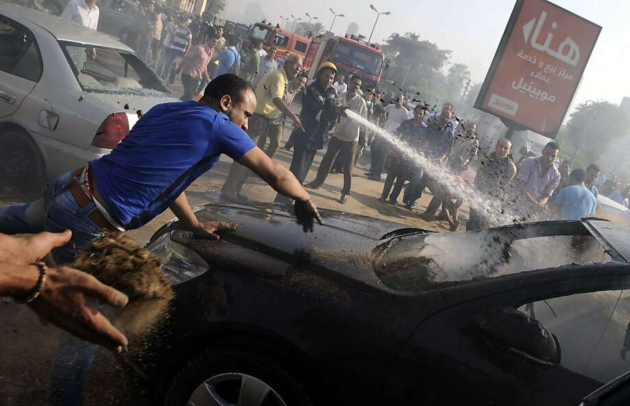 Egyptian firefighters and bystanders try to extinguish several cars that caught on fire outside the Nile City Towers during clashes between Egyptian policemen and an unknown mob from a near by neighbourhood in Cairo on August 2, 2012. 16 people were wounded in sectarian clashes on August 1, when angry Muslims attacked a church and Christian homes outside Cairo, after a Muslim died of wounds from a fight with a Christian. AFP PHOTO/MOHAMED HOSSAMMOHAMED HOSSAM/AFP/GettyImages Photo: Mohamed Hossam, AFP/Getty Images