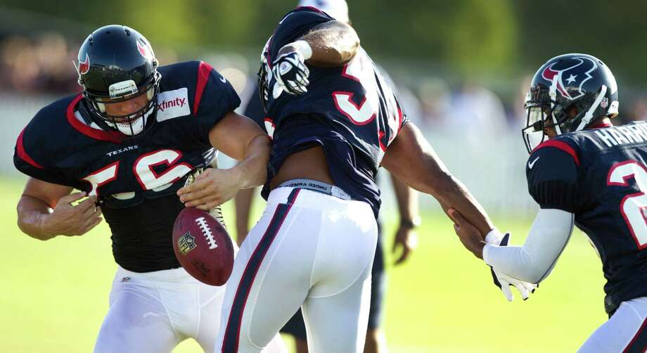 Houston Texans linebacker Brian Cushing (56) pulls the ball away from inebacker Bradie James (53) during a turnover drill at Texans training camp at the Methodist Training Center Wednesday, Aug. 1, 2012, in Houston. Photo: Brett Coomer, Houston Chronicle / © 2012 Houston Chronicle