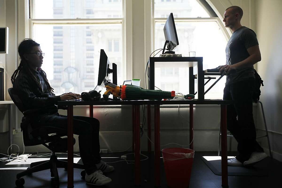 Derek P. Collins (right) prefers to stand while Nemo Chu rather sits in his ergonomical chair during work. A growing number of workplaces are letting their employees use standing desks to alleviate back pain and improve blood circulation. Web analytics company KISSMetrics is one of them in San Francisco, Calif. on Monday, July 30, 2012.