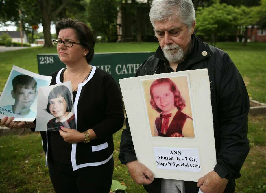FILE PHOTO     Helen McGonigle, left of Brookfield, and Jim Alvord of Norwalk, hold photos of sexual abuse victims during a May press conference outside the Catholic Center at 238 Jewett Avenue in Bridgeport. Protesters delivered a letter to Bishop William Lori asking that the diocese not appeal a Supreme Court decision to release documents in clergy sex abuse cases. Photo: Brian A. Pounds / Connecticut Post
