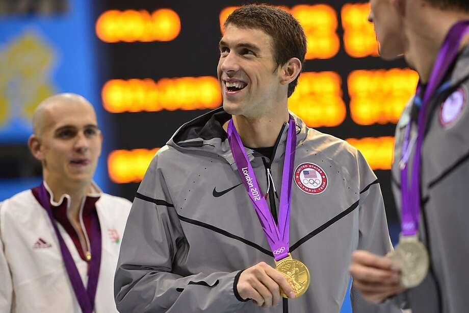 US swimmer Michael Phelps (C) shows off his gold medal after he won the men's 200m individual medely final swimming event at the London 2012 Olympic Games on August 2, 2012 in London.   AFP PHOTO / FABRICE COFFRINIFABRICE COFFRINI/AFP/GettyImages Photo: Fabrice Coffrini, AFP/Getty Images